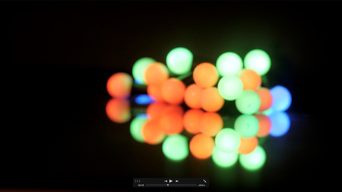 Multicolored decorative Christmas lights blinking brightly in a dark background