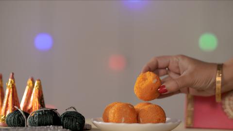 Female's hand keeping half-eaten Bundi laddu in a plate