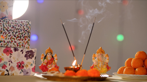 Beautiful prayer scene with Diya and incense sticks in front of Hindu god idols