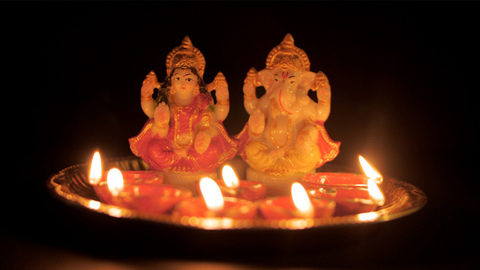 Close-up shot of Laxmi-Ganesh idol/murti on a puja plate with lighted Diyas