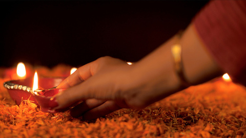 Woman's hand lighting decorative colorful Diyas for  Diwali - Hindu festival
