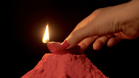 Beautiful hands of a woman keeping a lighted Puja Diya on a heap of rangoli color