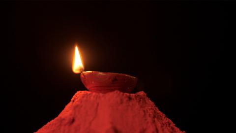 A lighted earthen oil lamp on a heap of powder color - Diwali rangoli concept
