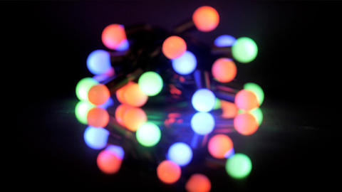 Glowing multicolored Christmas light against the dark studio background