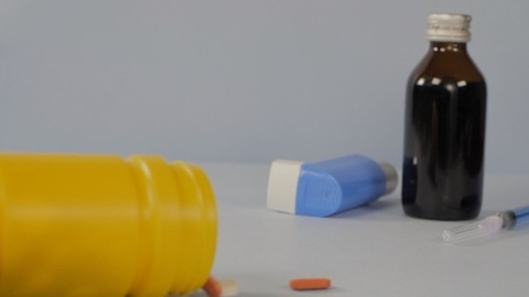 Slow-motion shot of orange-colored pills falling out of a yellow medicine bottle