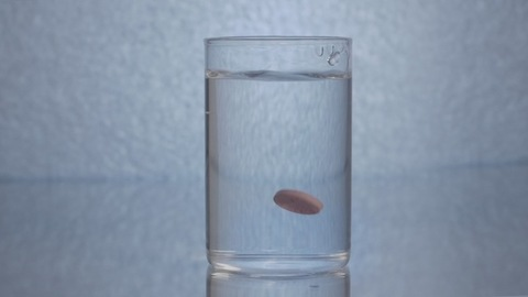Medicinal and healthcare concept - an orange pill dropping in a glass of water