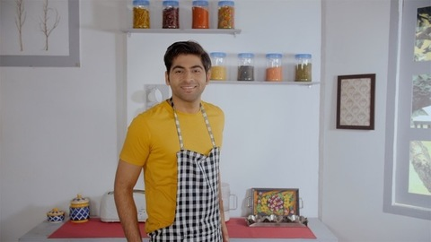 Modern Indian man preparing for cooking and tying an apron inside the kitchen