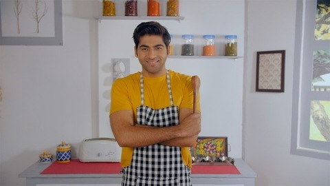 Attractive male home chef smiling confidently with a wooden spatula in his hand