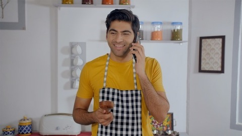 Smiling young Indian boy inside the kitchen - wearing casuals and talking on the phone