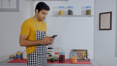 Young husband alone at home checking the recipe on mobile to cook his meal