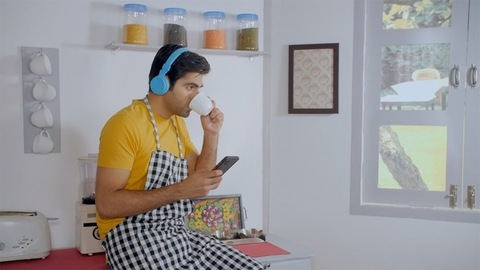 Portrait of an Indian adult wearing a headphone listening to soothing music