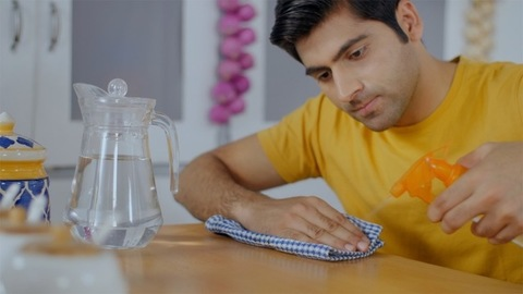 Young adult cleaning his kitchen counter - household hygienic activity