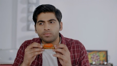 Attractive Indian male preparing and eating bread with tomato/sandwich for breakfast