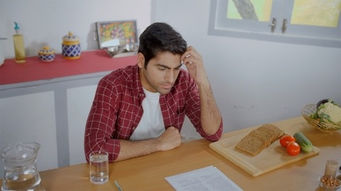 A frustrated man going through papers and forms and throwing them on a table