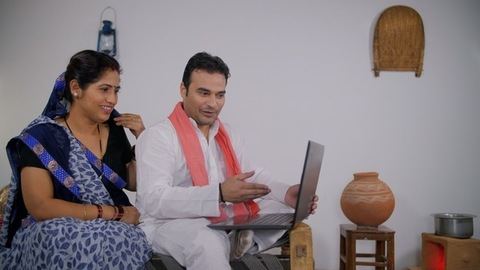 Educated Indian villager happily showing new things to his wife on a laptop