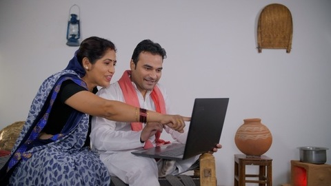 Village scene - Middle-aged husband-wife ordering things online using a laptop