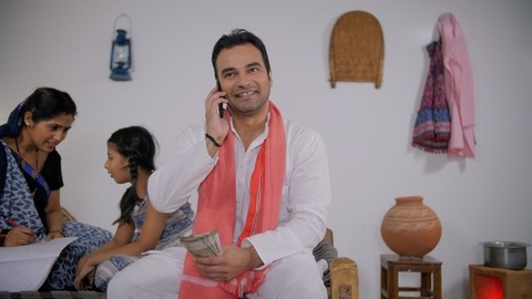 Indian villager taking a phone call about receiving money - financial concept