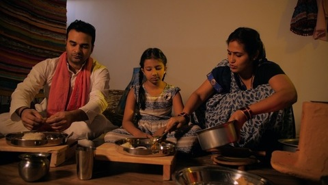 Middle-aged Indian housewife happily cooking and serving food to her family