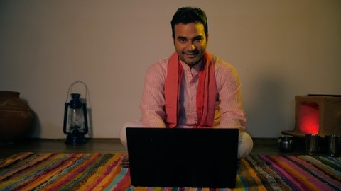 Confident young villager working on a laptop - progressive Indian farmer