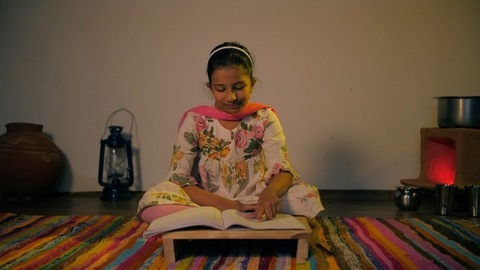 Village scene of an Indian girl reading her school book while sitting on the floor