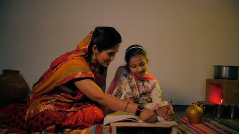Small village daughter happily studying with her mother - girl child's education