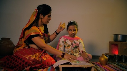 Mother scolding daughter while helping her in studies - education concept