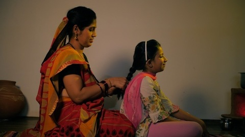 Happy Indian housewife braiding child's hair - mother-daughter bonding