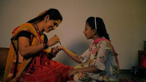 Village lady applying Mehendi on child's hand - mother-daughter bonding