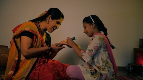 Small daughter of a villager applying Mehendi/Henna on her mother's hand