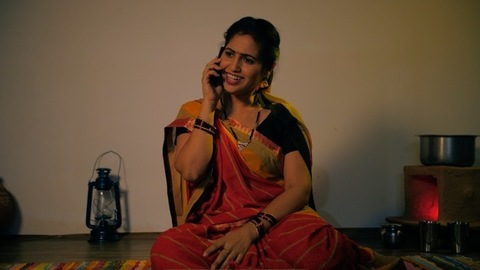 Attractive female farmer happily chatting on her smartphone at home