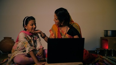 Young mother learning to run a laptop from her daughter - modern villager