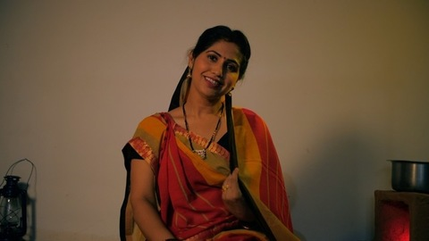 Pretty village woman adjusting her saree Pallu/Ghunghat while sitting in the kitchen