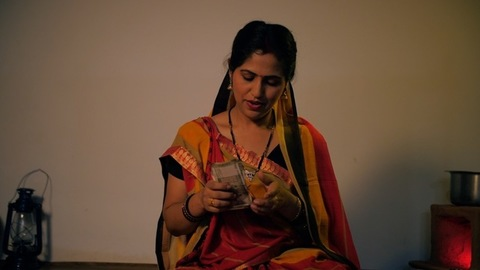 Happy village housewife counting her earnings - home finance concept