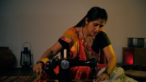 Indian village woman making clothes on her old hand sewing machine