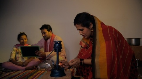 Village housewife lighting a lantern while her husband and daughter studying - Nuclear village family