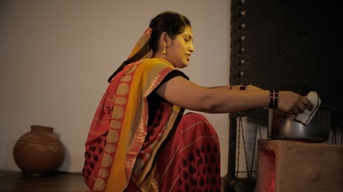 Indian traditional mother happily cooking food in a pot - village lifestyle concept