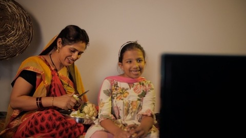Young housewife from a village watching television with her daughter at home