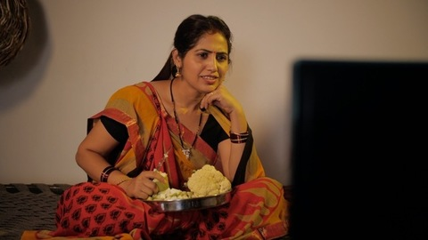 Indian housewife happily watching a TV program while cutting vegetables