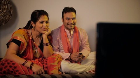 Young village couple is happily watching a TV program while sitting on a chaarpai
