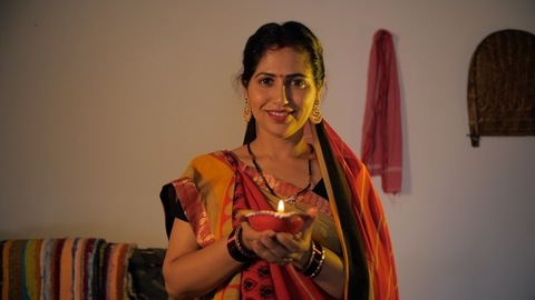 Portrait of a beautiful Indian village woman holding a Diya during Diwali festival