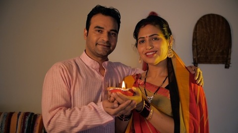 Village scene of an Indian married couple happily holding a burning clay lamp