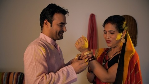 Handsome man gifting gold bangles to his beautiful wife on the Diwali festival