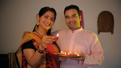 Married village couple happily celebrating Diwali festival together at home
