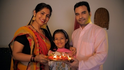 Village scene of an Indian family happily doing aarti / arti - Puja at home