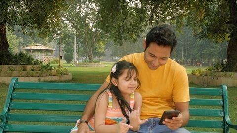 Handsome Indian father and his little girl scrolling their smartphone in the park