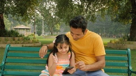 Child and her dad sitting on a bench outdoors while playing games on mobile