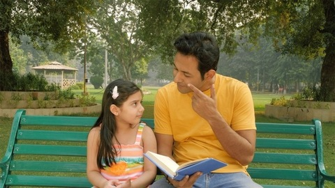 Caring dad reading out an interesting story to his little child sitting outdoors