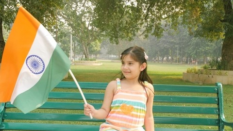 School going Indian girl waving the flag of India - Independence day / Republic day