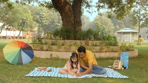 Father-daughter duo drawing a scenery sitting outdoors under a tree in the park