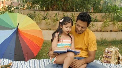 Lovely girl child reading a storybook while sitting on her father's lap outdoors